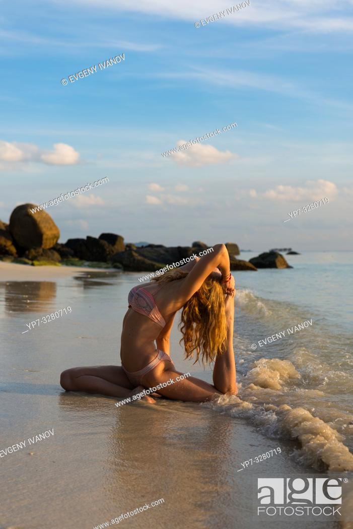 Stock Photo: Thai beach yoga - girl in pigeon pose on Ko Lipe island, Thailand.