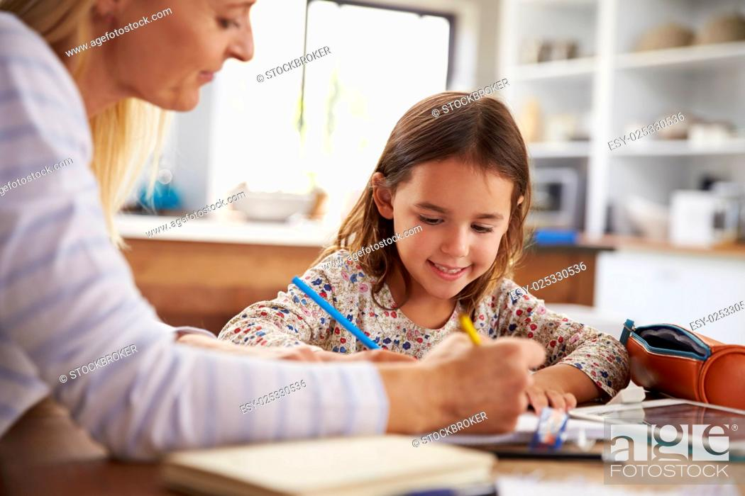 Stock Photo: Mother teaching her daughter at home.