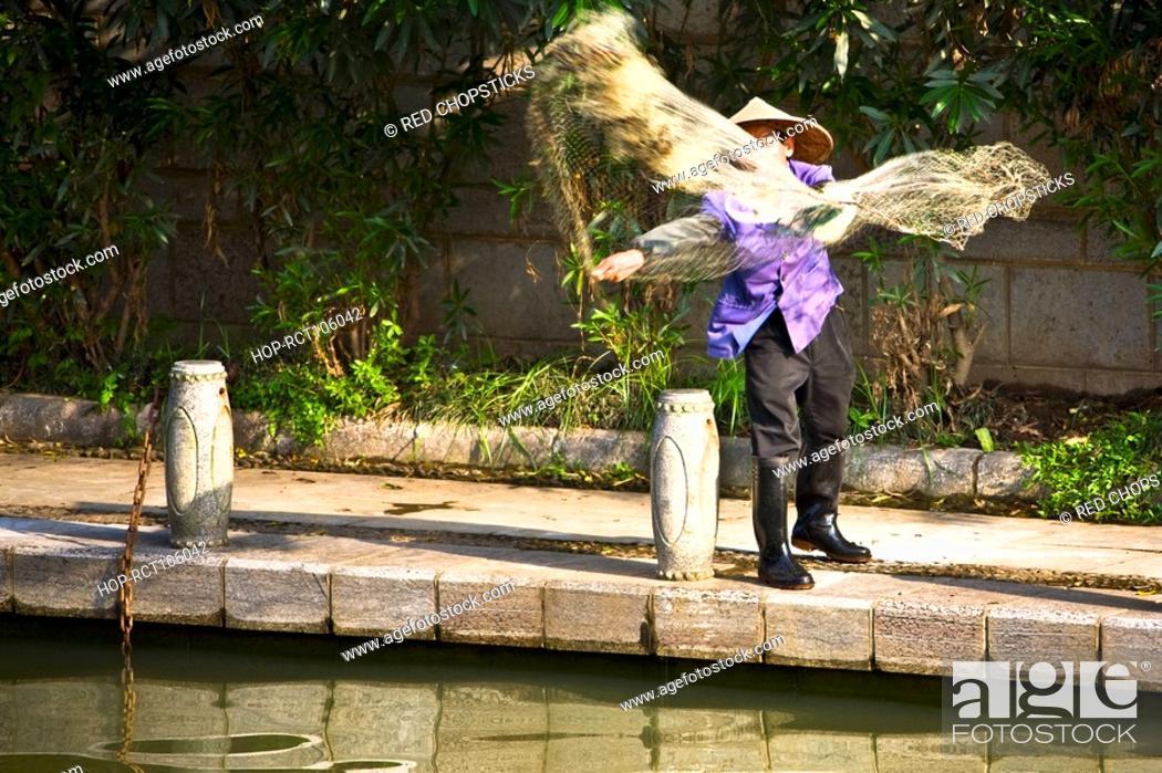 Stock Photo: Fisherman throwing a fishing net in a lake, Guilin, Guangxi Province, China.