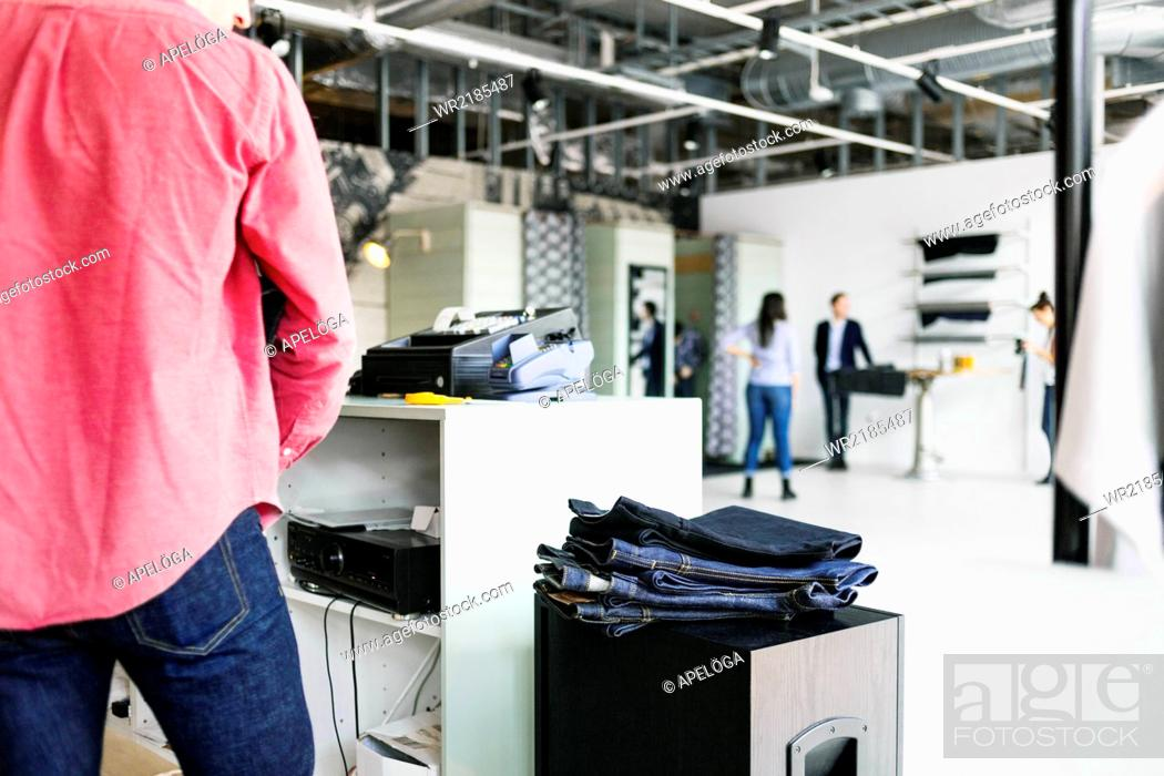 Stock Photo: Midsection of cashier at counter in jeans factory.