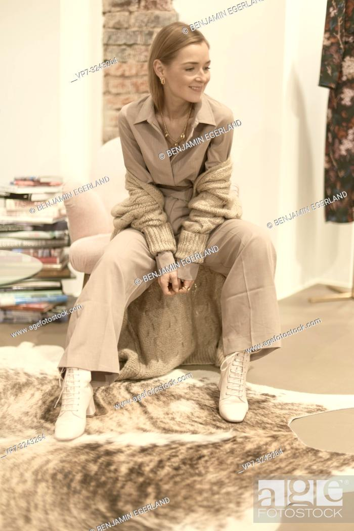 Imagen: trendy woman in beige fashion outfit sitting in armchair indoors, women's style trend, in Munich, Germany.