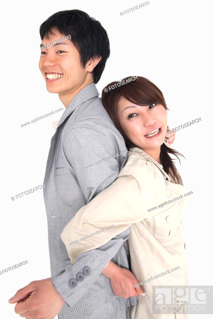 Stock Photo: Couple standing back to back.