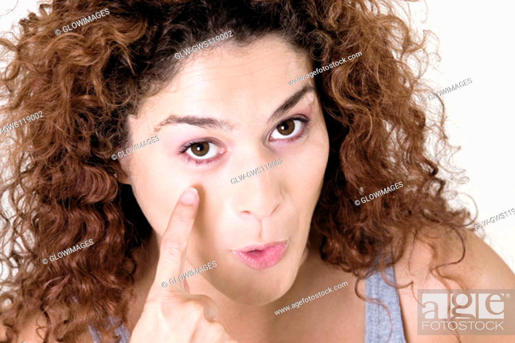 Stock Photo: Portrait of a young woman pointing at her eye.