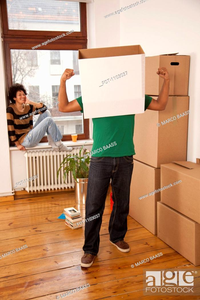 Stock Photo: A man with a box on his head flexing his muscles while woman watches.