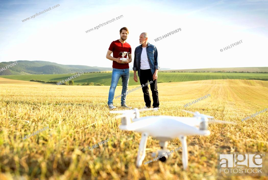 Stock Photo: Senior father and his adult son with drone on a field.