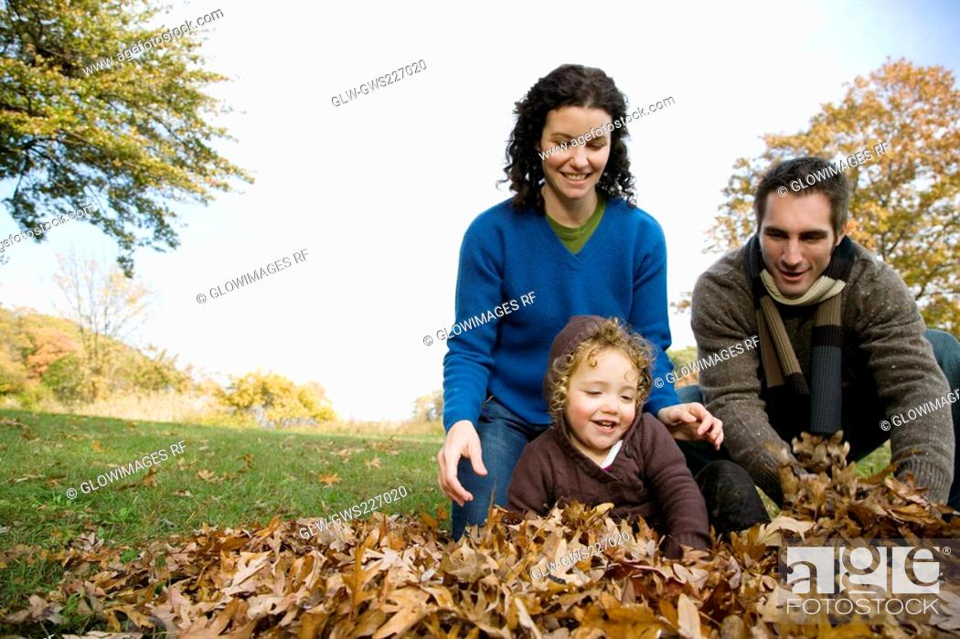Stock Photo: Couple with their daughter in a garden.