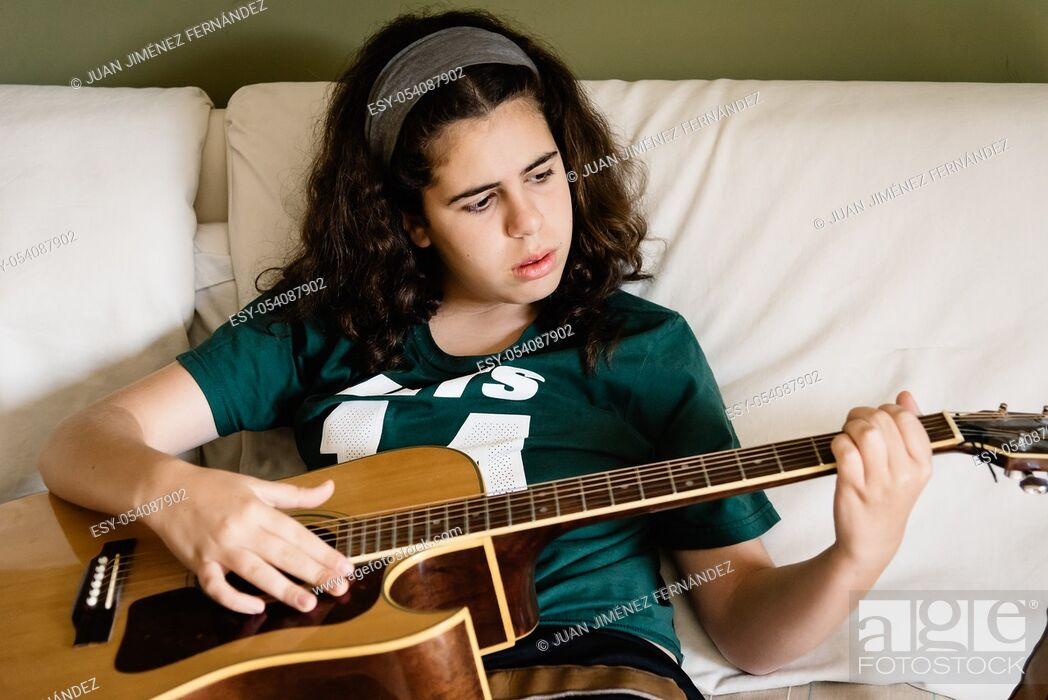 Stock Photo: Girl practicing chords on acoustic guitar at home sitting on bed.