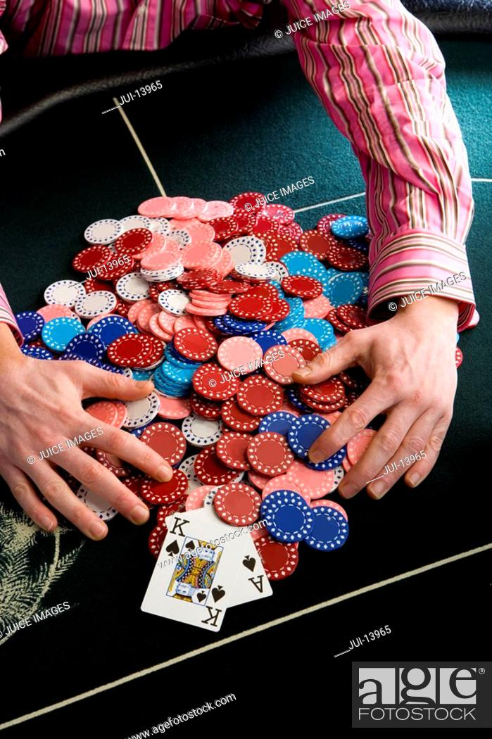 Stock Photo: Man collecting pile of gambling chips on table, mid section, elevated view.