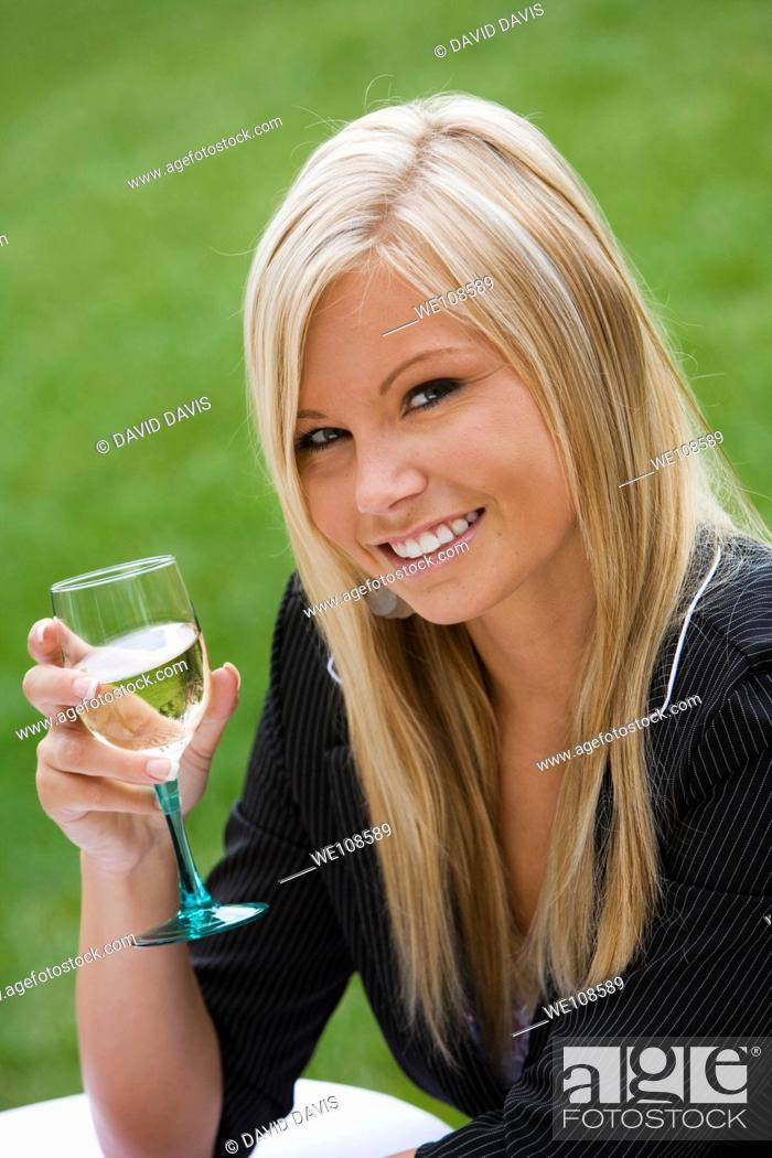 Stock Photo: Young woman relaxing with a glass of wine in an outdoor cafe.