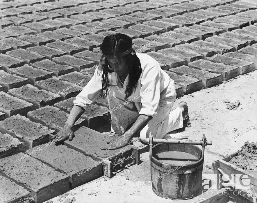Stock Photo: California: c. 1930 .The padres taught the Indians to make the adobe bricks used in the building of the missions. When the mold was full the mud was patted.