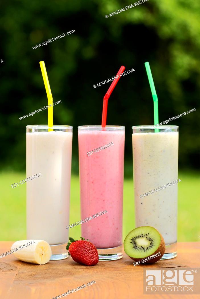Stock Photo: Banana, strawberry and kiwi milkshake on a garden table. Focus on fruits, shallow DOF.