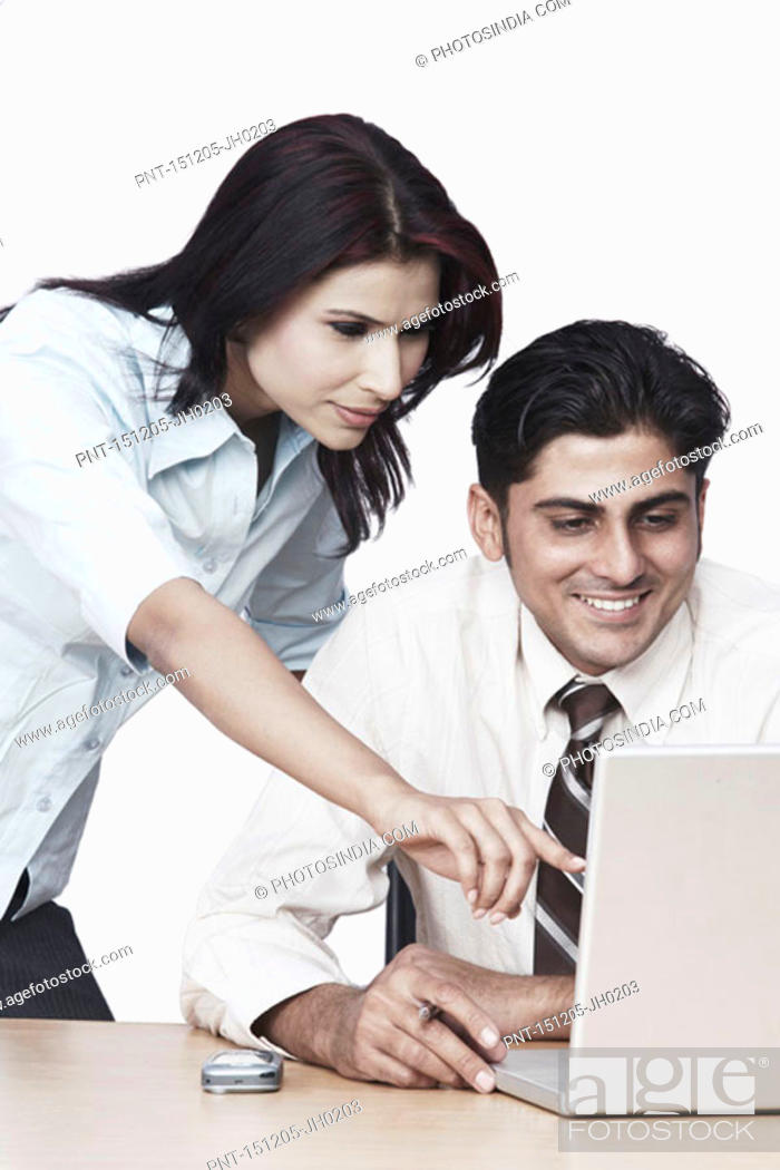 Stock Photo: Businessman and a businesswoman using a laptop.