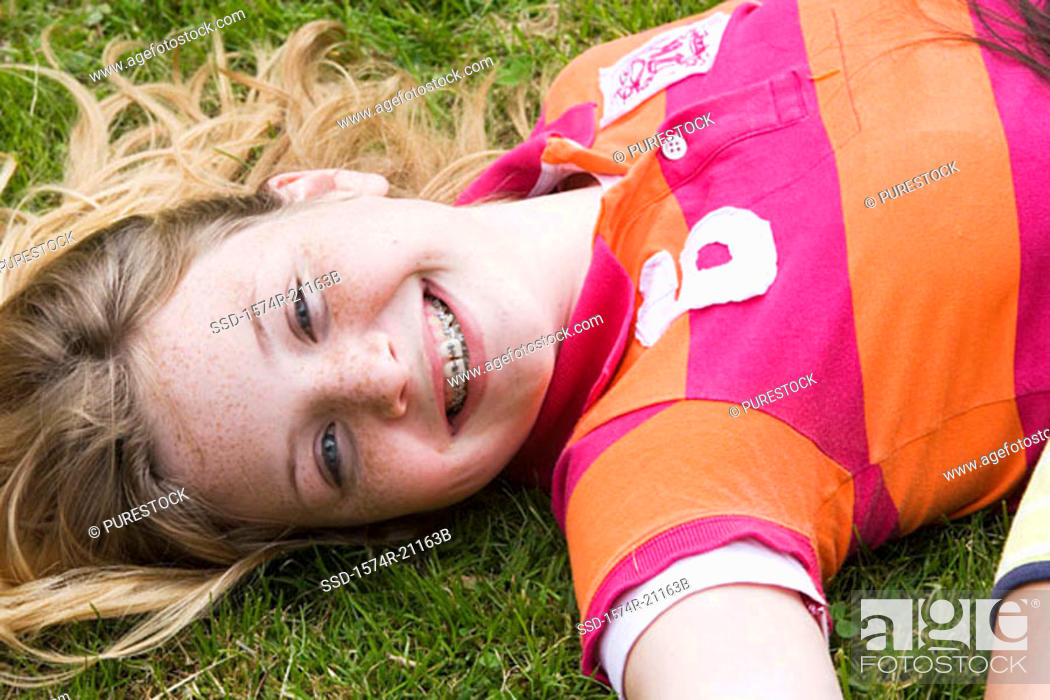 Stock Photo: Portrait of a girl lying on the grass and smiling.