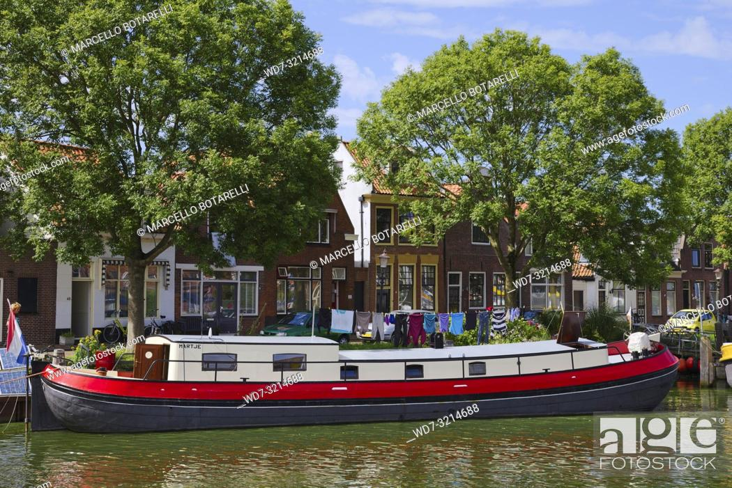 Stock Photo: House boat in Enkhuizen, small city of northern Holland, boat transformed into home, behind traditional houses.
