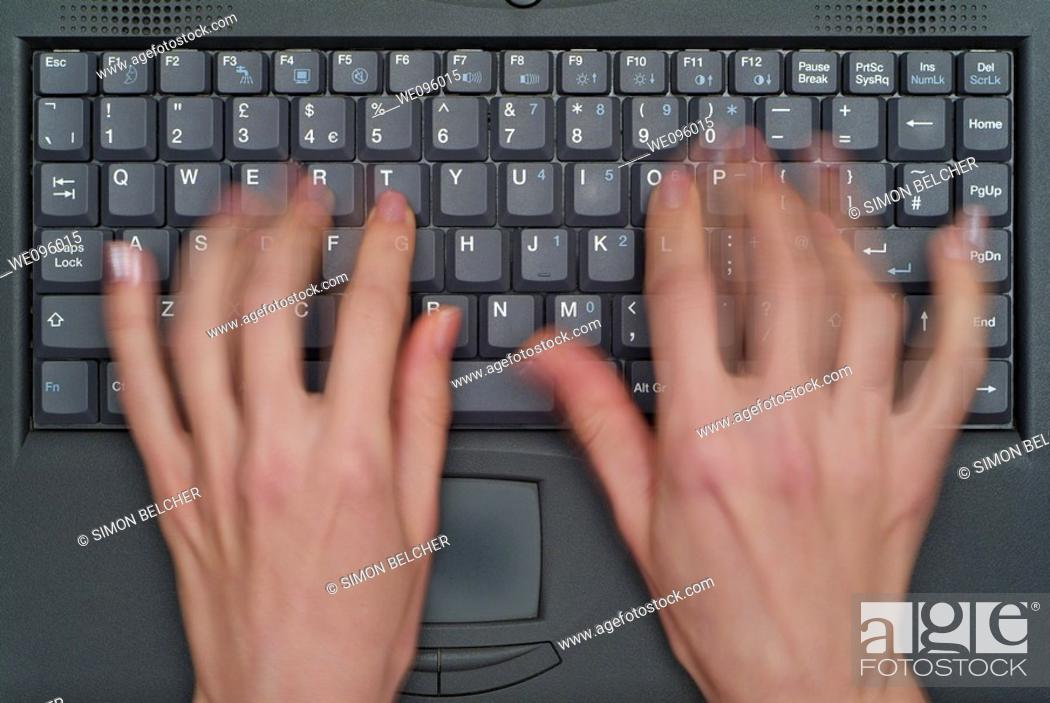 Stock Photo: Blurred Motion of a Womans Fingers as She Types on the Keyboard of a Laptop Computer.