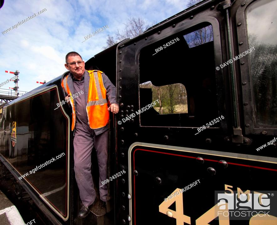 Stock Photo: train driver climbs on board steam locomotive at Grosmont station,on The North Yorkshire Moors Railway,Yorkshire,UK.