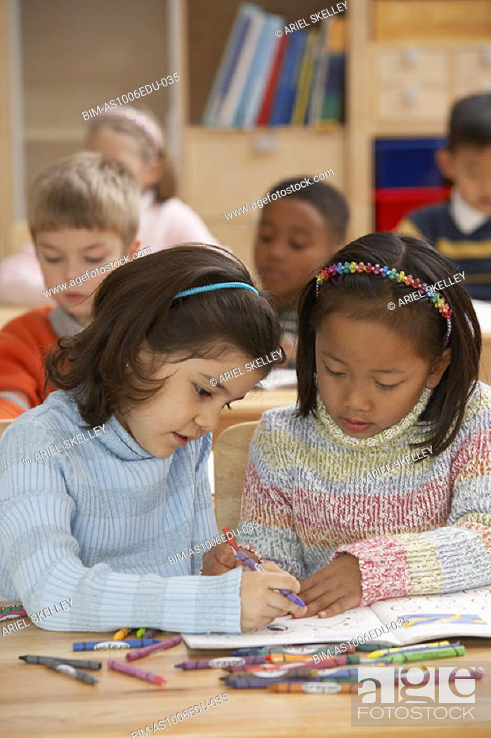 Stock Photo: Two girls coloring in classroom.