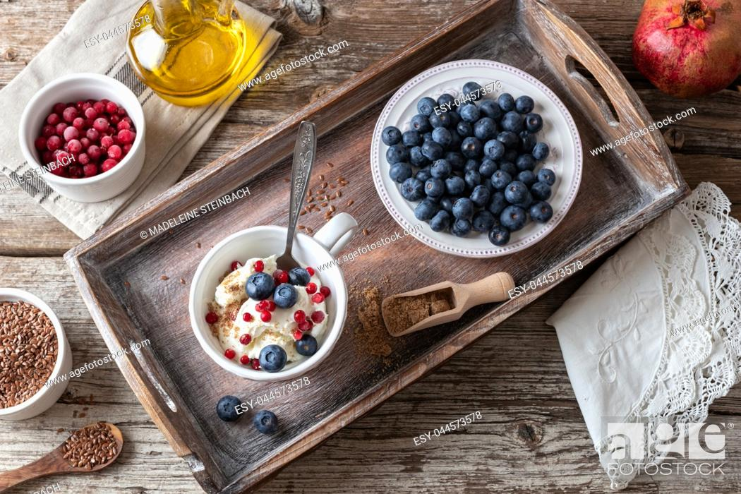 Stock Photo: A cup of cottage cheese with ground linseeds, blueberries and frozen cranberries, with red currants and flax seed oil in the background.