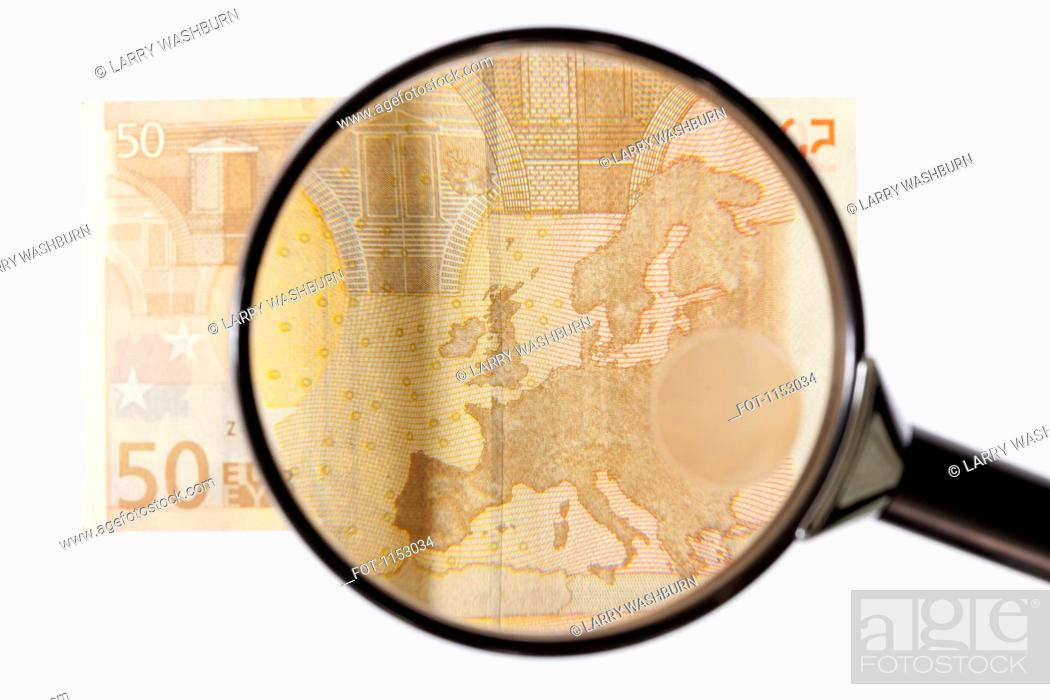 Stock Photo: A magnifying glass magnifying a fifty Euro banknote.