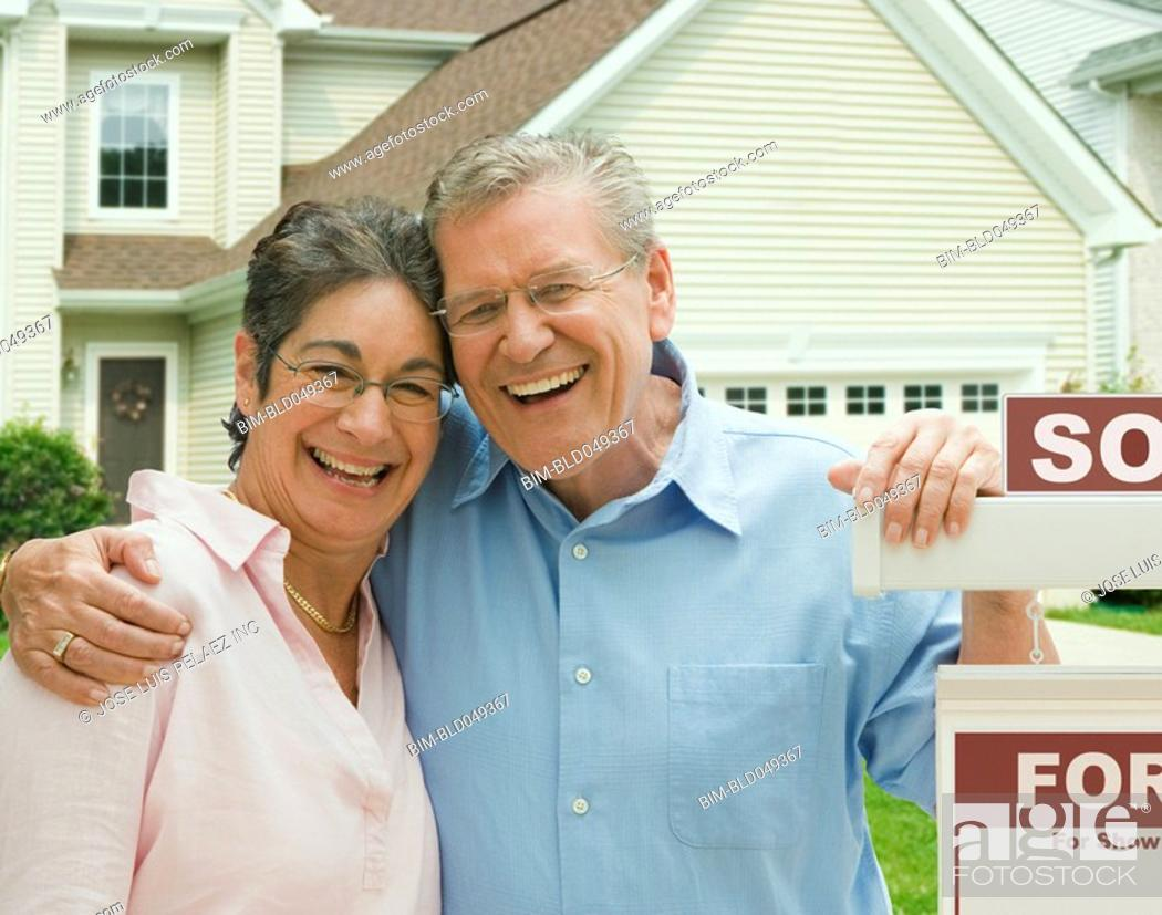 Stock Photo: Senior couple in front of new house.