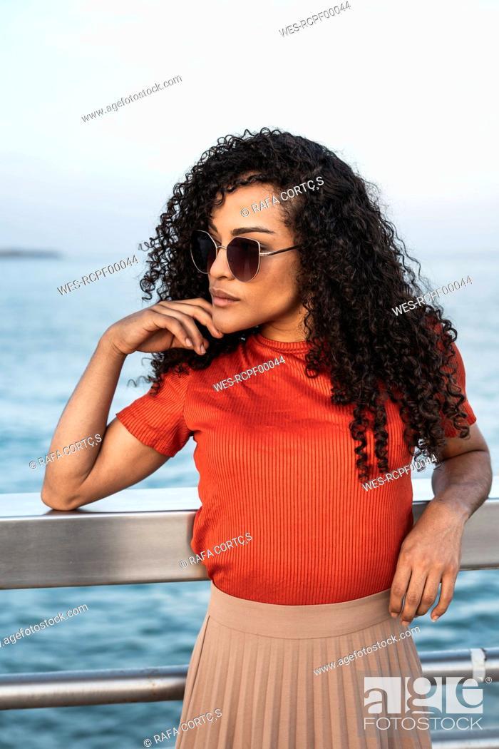 Stock Photo: Beautiful woman, wearing sunglasses, leaning on railing by the sea.