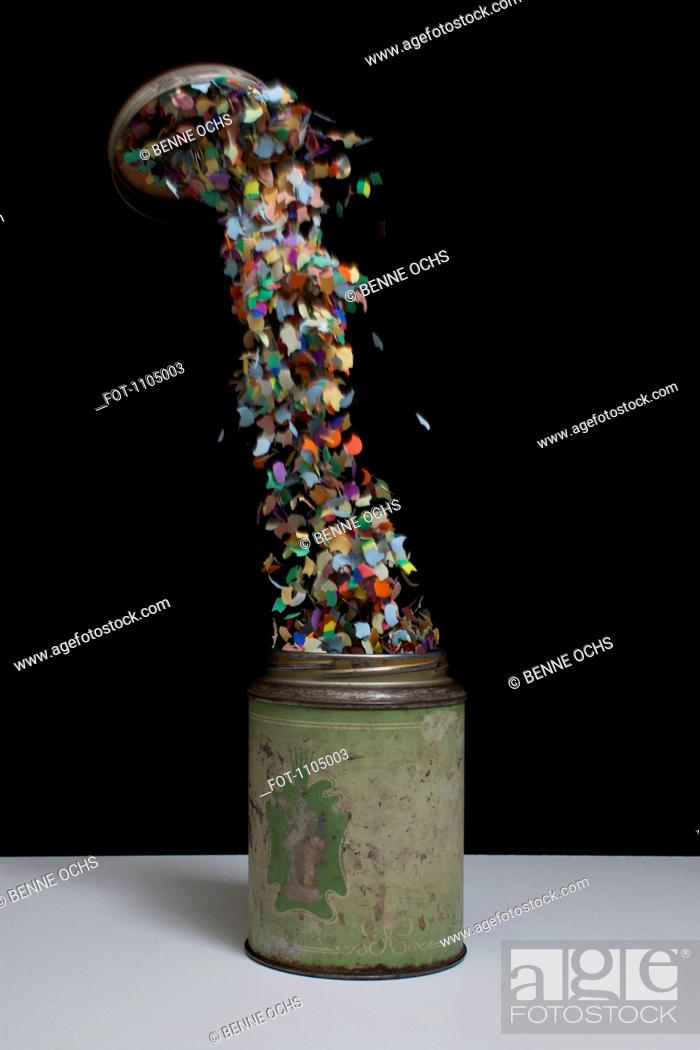 Stock Photo: Confetti flying out of an old-fashioned metal tin.
