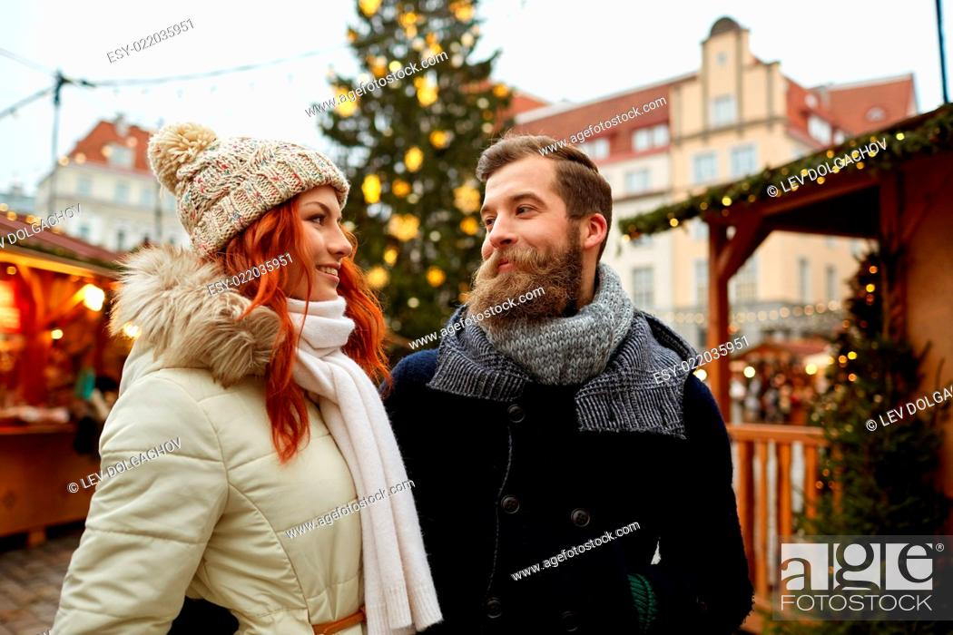 Imagen: holidays, winter, christmas, tourism and people concept - happy couple in warm clothes walking in old town.