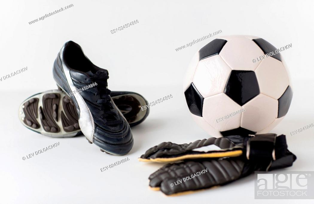 Stock Photo: sport, soccer, football and sports equipment concept - close up of ball, boots and goalkeeper gloves.