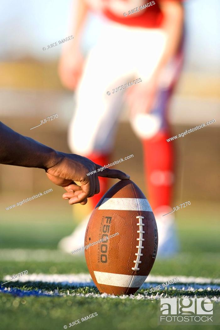 Stock Photo: American football player attempting to kick field goal, focus on teammate holding ball vertically against pitch in foreground surface level.