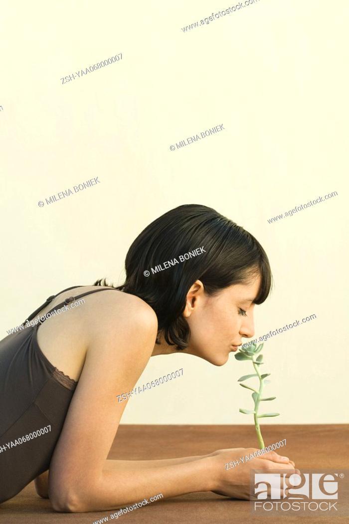 Stock Photo: Woman smelling sedum plant, eyes closed, side view.