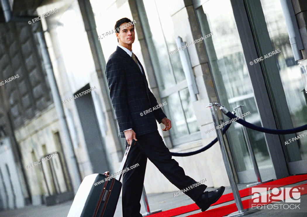 Stock Photo: Businessman walking with luggage outside, side view.