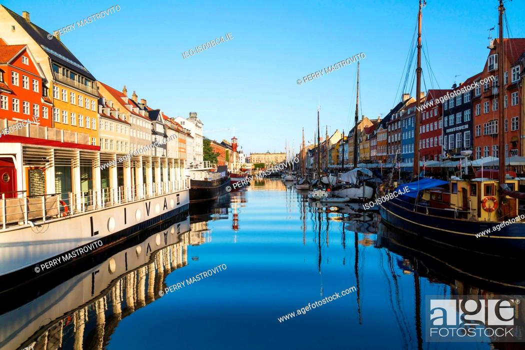 Stock Photo: Moored restaurant boat and colourful 17th century town houses on Nyhavn canal, Copenhagen, Denmark.