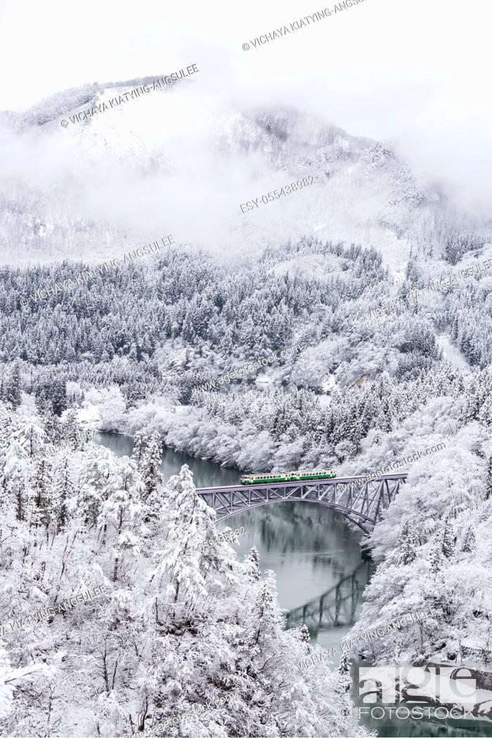 Imagen: Winter landscape snow covered trees with train crossin River on Bridge.