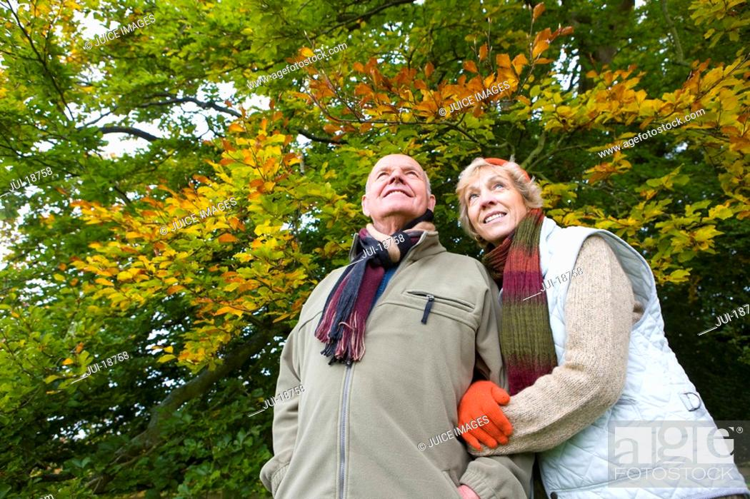 Stock Photo: Couple wearing scarves and standing in front of trees.