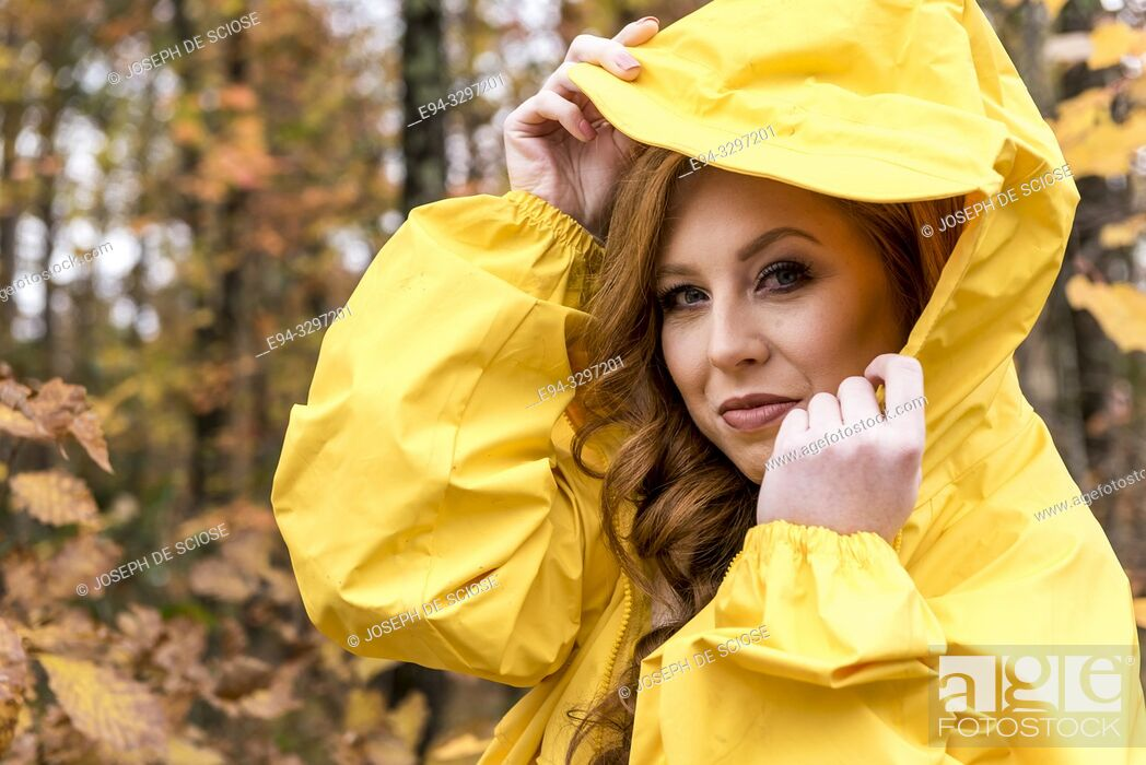 Stock Photo: A 25 year old redheaded woman wearing a yellow jacket outdoors in the autumn.