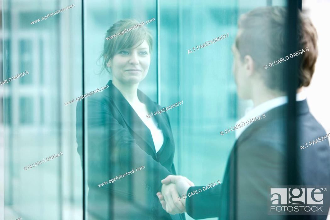 Stock Photo: Businesswoman and businessman meet and shake hands at building entrance.