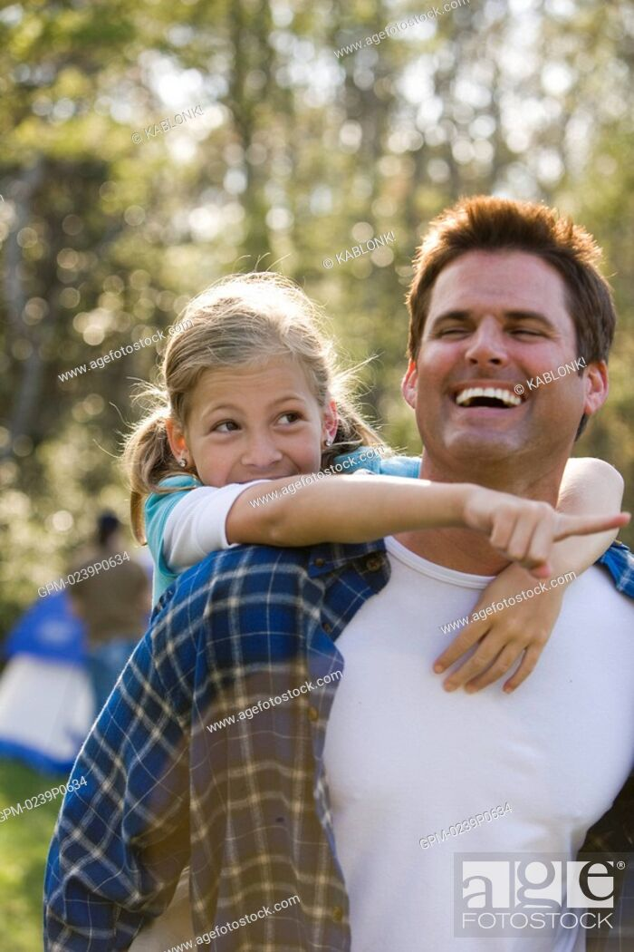 Imagen: Father piggybacking daughter in park, smiling.