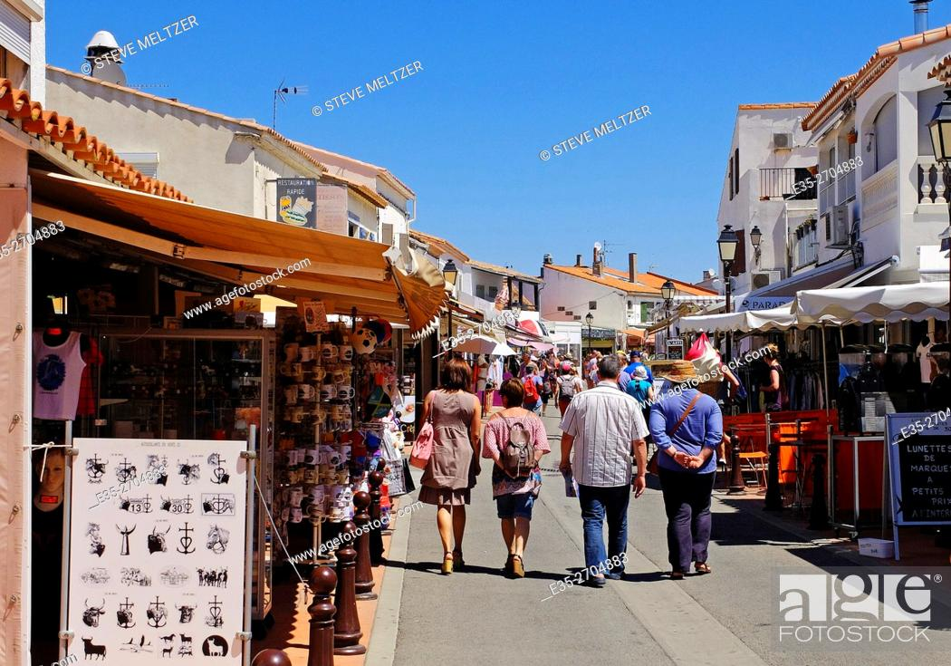 Stock Photo: Tourists stroll through the shops in the center of les Saintes-Marie de la mer.