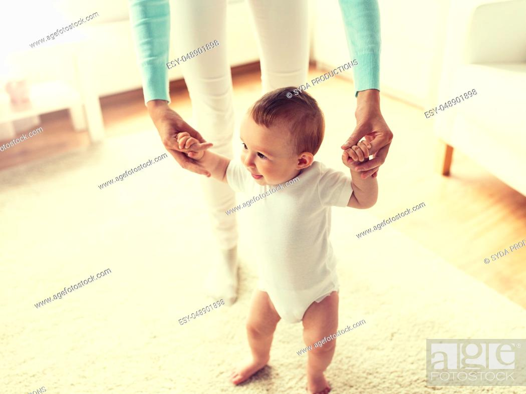 Stock Photo: happy baby learning to walk with mother help.
