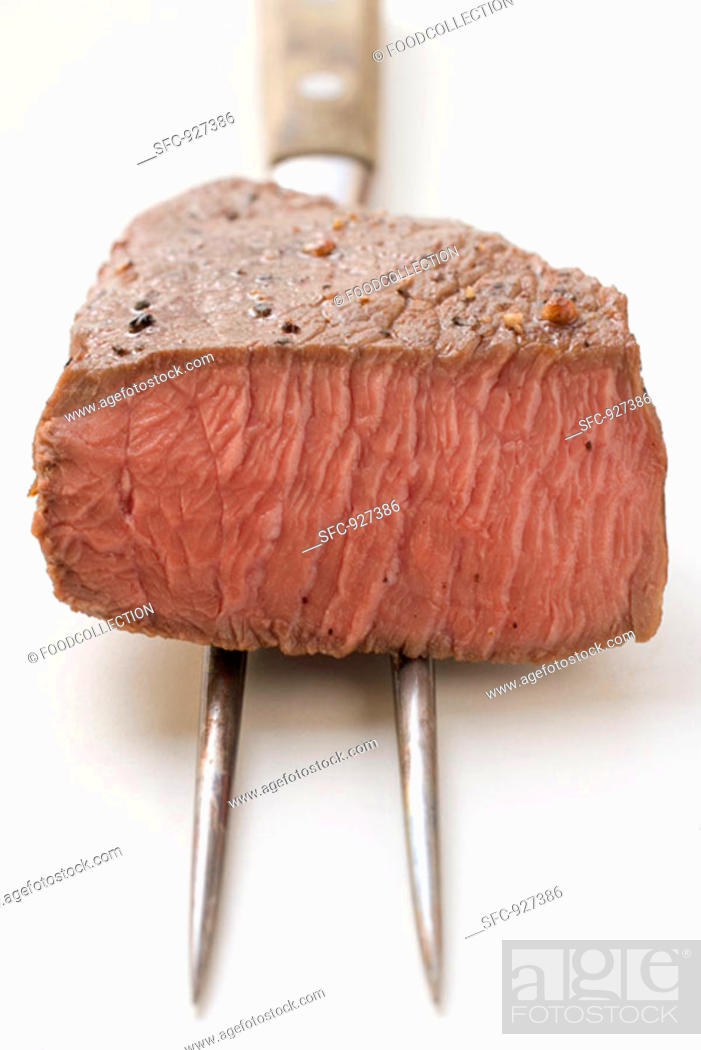 Stock Photo: Beef steak, a piece cut off, on meat fork.