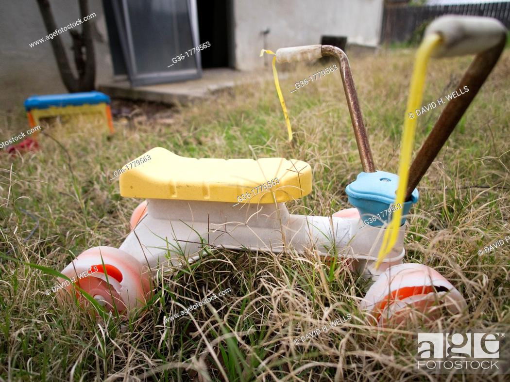 Stock Photo: Childrens tricycle abandoned in the grass of a foreclosed home in Fresno, California, United States.