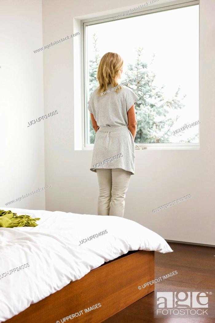 Stock Photo: Woman staring out bedroom window.