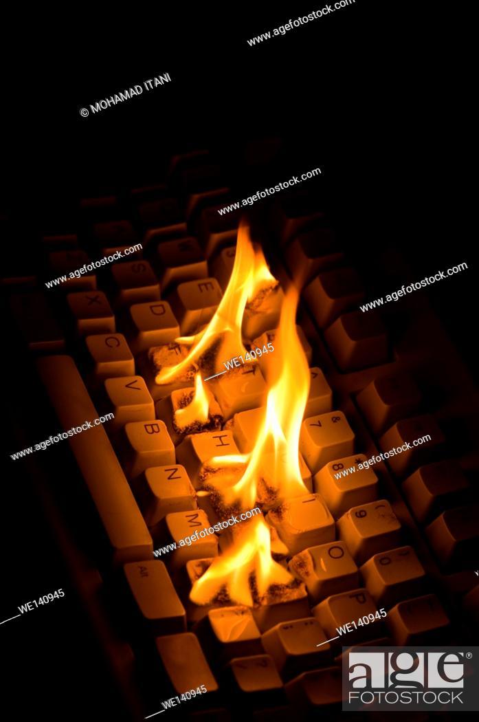 Stock Photo: Computer Keyboard burning indoors.