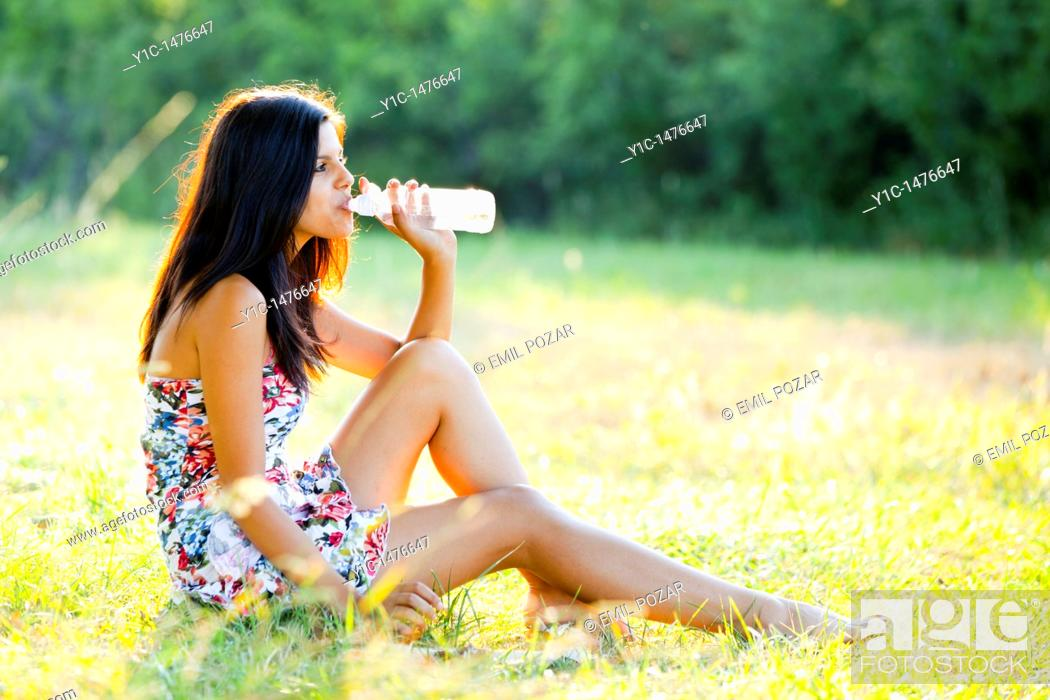 Stock Photo: Attractive young woman with a bottle of water on the grass.