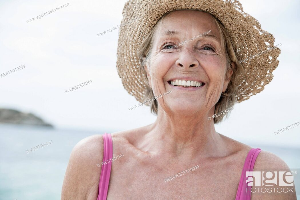 Stock Photo: Spain, Senior woman with straw hat on beach.