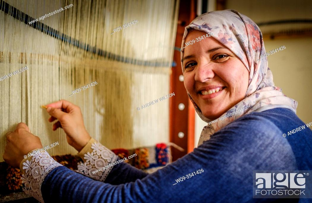 Stock Photo: A young Berber woman weaving a carpet in Tazenakht, southern Morocco, North Africa.