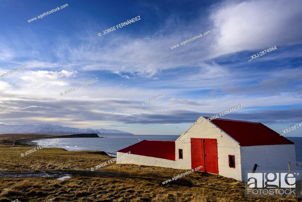Stock Photo: Colourful farm with red roof and door at sunset.