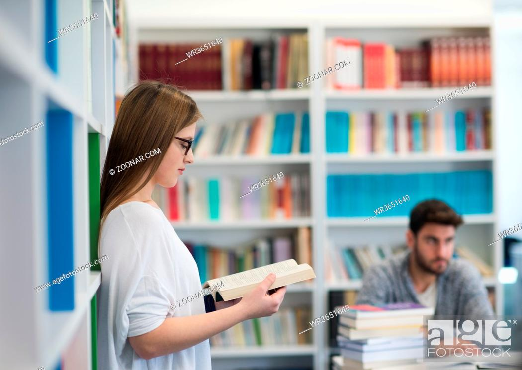 Stock Photo: happy students couple in school library have discussion about book.