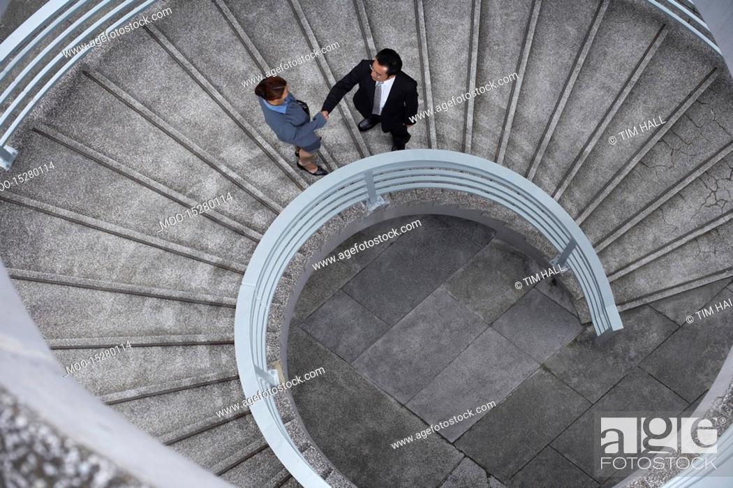 Stock Photo: China Hong Kong two business people shaking hands standing on spiral staircase view from above.