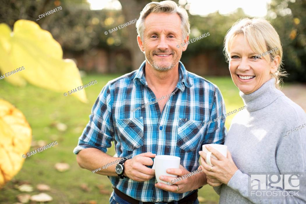 Stock Photo: Portrait smiling, confident mature couple drinking coffee in autumn yard.
